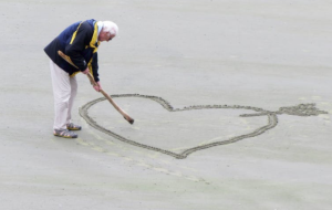 2017-08-06 16_54_00-Man Wearing Blue Jacket Holding a Brown Stick Towards the Heart Drawn on Sand ·
